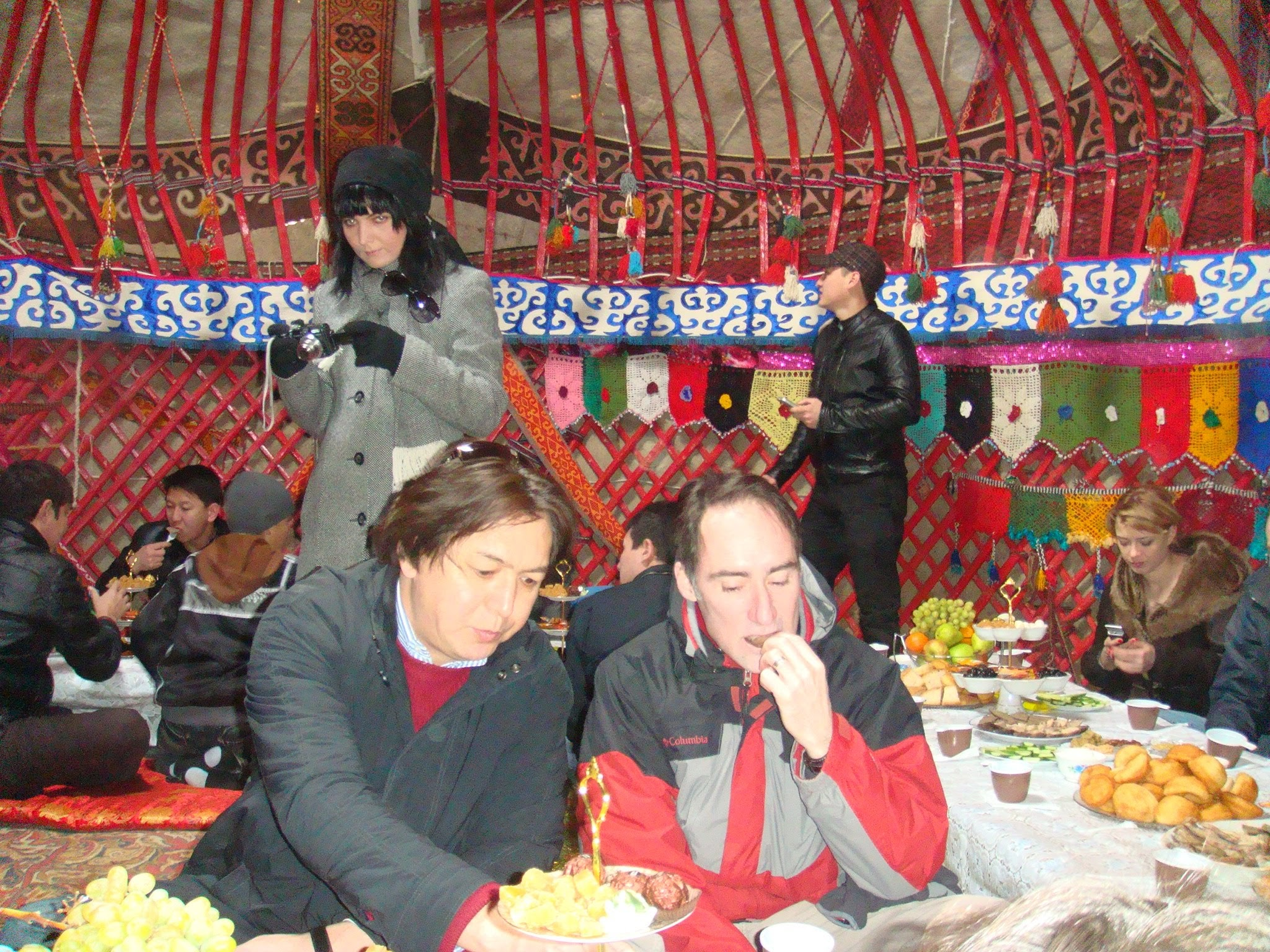 Professor Buford and several other people eating food inside a colorful yurt