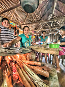 four women cooking inside a wooden structure